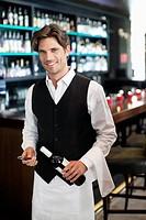 Portrait of smiling sommelier holding bottle of wine in bar