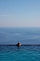 Girl looking at horizon from pool