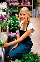 Lovely young florist working in the flower shop among the plants _ portrait