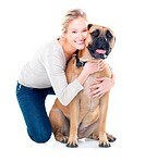 Pretty young woman smiling while embracing her bull mastiff _ isolated on white
