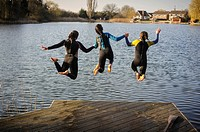 Three girls jumping into a lake while holding hands, England, UK