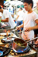 Chefs in a Thai restuarant preparing food on gas stovetops