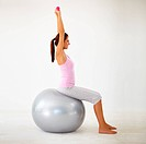 Side view of a young woman sitting on a physio ball while holding dumbbells above her head