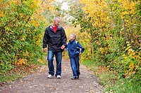 Father And Son Walking On A Path In A Park In Autumn, Edmonton Alberta Canada