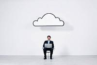 Businessman using laptop computer beneath cloud representing cloud computing