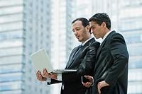 Business executives using laptop computer outdoors