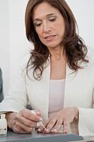 Mature woman in business attire applying nail polish