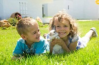 Boy and girl playing with a rabbit