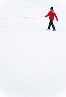 Woman with a leash walking in snowy landscape
