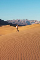 Woman photographer photographing sand waves
