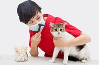 Female veterinarian examining cat´s ear with an otoscope device against gray background