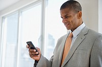 Mixed race businessman text messaging on cell phone