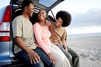 Family sitting on hatchback enjoying the beach