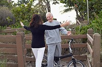Caucasian woman hugging man on bicycle