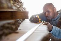 Black worker measuring wood