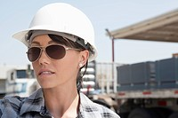 Close_up view of female industrial worker wearing hardhat and sunglasses