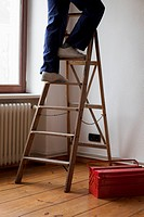 A man standing on a ladder, low section