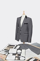 Suit on tailor´s dummy with design layouts over gray background