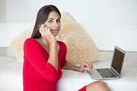 Woman in red on phone with laptop
