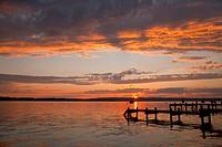 Sun setting over still rural lake