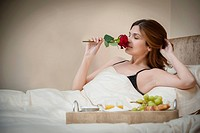 Woman relaxing with breakfast in bed