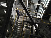 Worker climbing staircase in factory