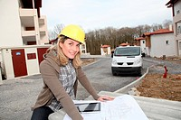 Woman engineer looking at plan on construction site