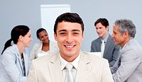 Smiling businessman sitting in front of his team in a meeting