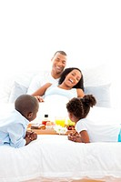 Cheerful family having breakfast in the bedroom