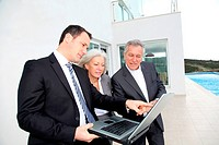 Senior couple visiting luxury villa with real_estate agent