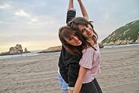 Two happy young women at El Sablón beach, Asturias, Spain