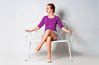 Pin up girl sitting on bench and smiling