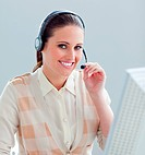 Charming businesswoman working at a computer with headset on
