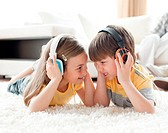 Siblings playing on the floor with headphones