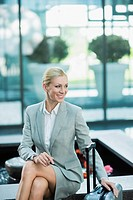 Germany, Stuttgart, Businesswoman sitting with wheeled luggage, smiling