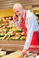 Germany, Cologne, Mature man talking on phone in supermarket