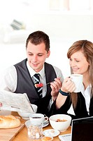 Smiling couple of business people reading a newspaper while having breakfast