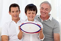 Son holding a rugby ball with his father and grandfather