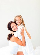 Cute mother and her daughter looking at the camera on the bed
