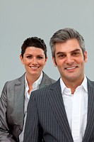 Businesswoman and businessman smiling at the camera