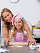 Mother and daughter baking Christmas cookies in the kitchen