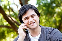 Beautiful brunette men calling by mobile at outdoor.
