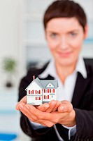 Portrait of a businesswoman holding a miniature house