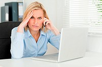 Frustrated blonde businesswoman on phone looks into camera