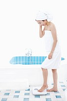 A woman with bath towel around her body and over head weighing herself on a scale