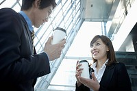 Businessman and woman discussing with coffee in their hands
