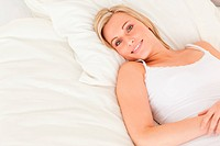 Blonde woman lying on her bed