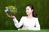 woman holding a sphere covered with colorful butterflies