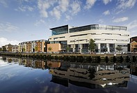 The Cork School of Music, Cork, Ireland. Architect: Murray O´Laoire, 2007. View of building from across river showing adjacent buildings.