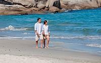 Couple walking on the beach under the sun